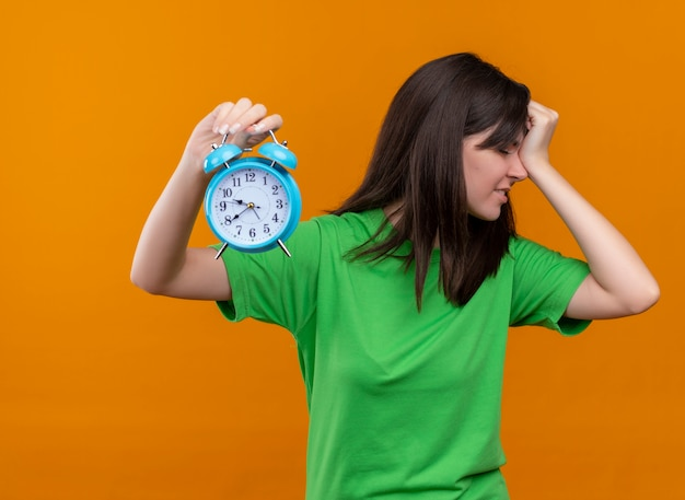 緑のシャツのイライラした若い白人の女の子は時計を保持し、孤立したオレンジ色の背景に頭に手を置きます 無料写真