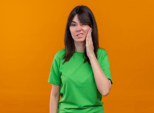 緑のシャツを着てイライラする若い白人の女の子は顔を保持し、孤立したオレンジ色の背景でカメラを見る 無料写真