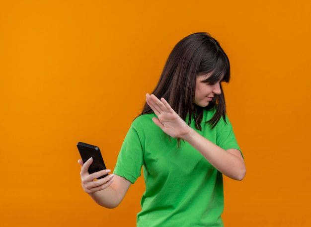 緑のシャツを着たイライラする若い白人の女の子は、コピースペースで孤立したオレンジ色の背景に電話とジェスチャーを保持していません 無料写真