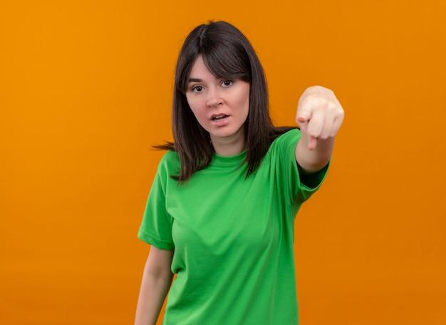 緑のシャツを着たイライラした若い白人の女の子は、孤立したオレンジ色の背景を前に指します 無料写真