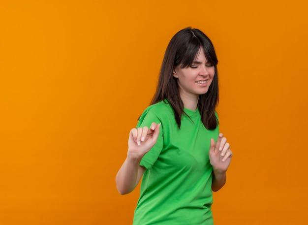 緑のシャツを着たイライラした若い白人の女の子は、コピースペースで孤立したオレンジ色の背景に何かを押すふりをします 無料写真