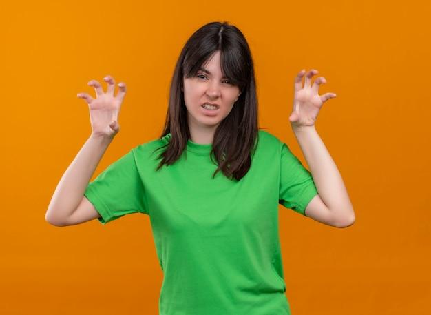 緑のシャツを着てイライラした若い白人の女の子が手を上げ、孤立したオレンジ色の背景でカメラを見る 無料写真