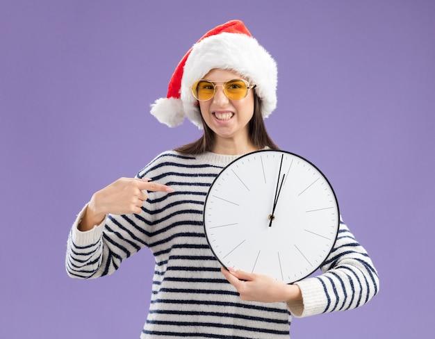 Infastidita giovane ragazza caucasica in occhiali da sole con cappello santa tenendo e indicando l'orologio Foto Gratuite