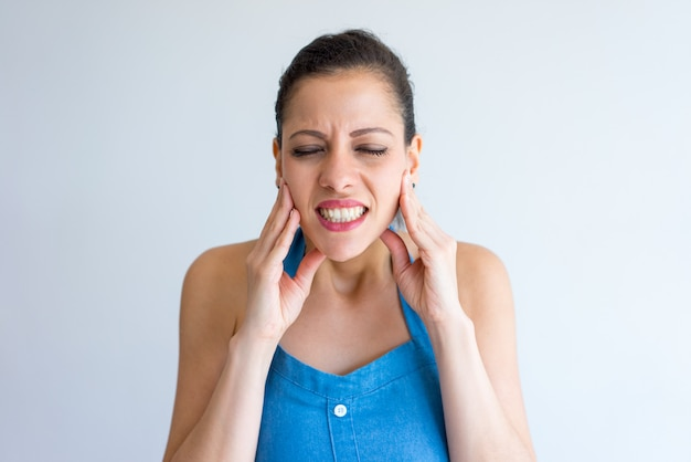 Annoyed young woman suffering from toothache and touching jaw. Free Photo