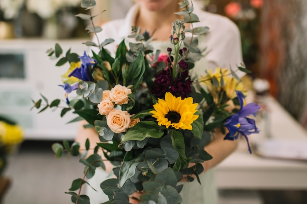 Anonymous florist holding bunch of flowers Free Photo