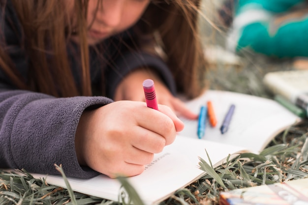 Anonymous girl drawing on grass Free Photo