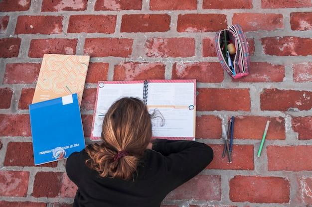 Anonymous girl studying on brick pavement Free Photo