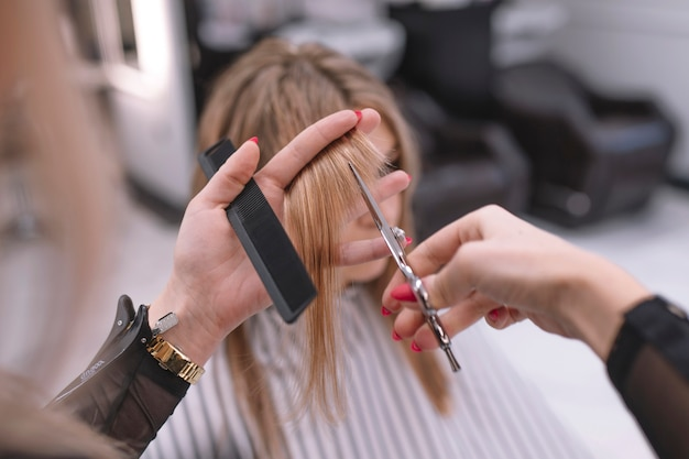 Anonymous hairdresser cutting hair of customer Free Photo