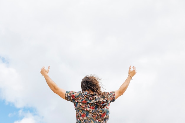 Anonymous male rising hands to cloudy sky Free Photo