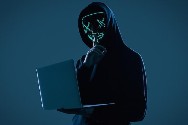 Pria anonim dengan hoodie hitam dan topeng neon meretas Foto Premium komputer