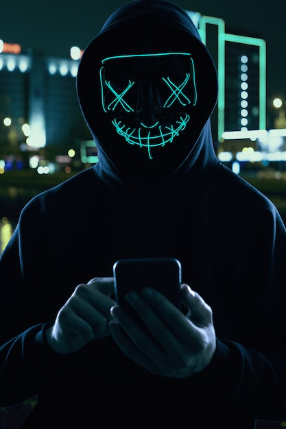 Premium Photo Anonymous Man In A Black Hoodie And Neon Mask Hacking Into A Smartphone