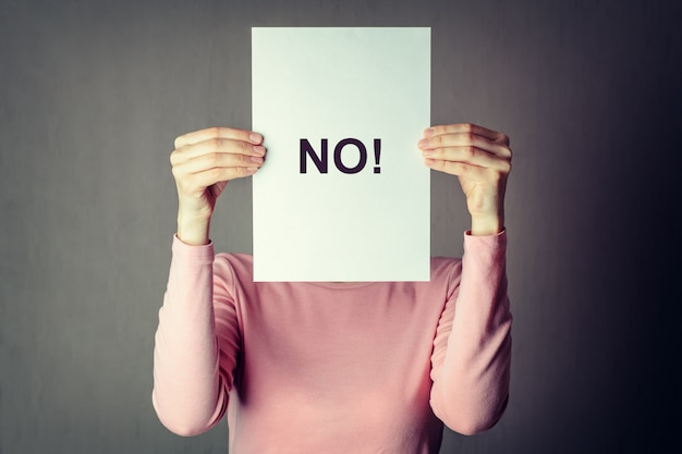 Anonymous woman covering face behind a white paper sheet with inscriprion word no Premium Photo