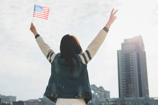 Anonymous woman raising hands and american flag in honor of independence day Free Photo