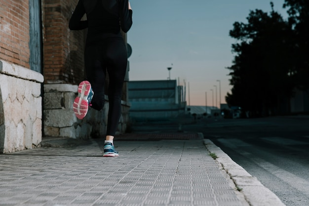 Anonymous woman running on street in dusk Free Photo