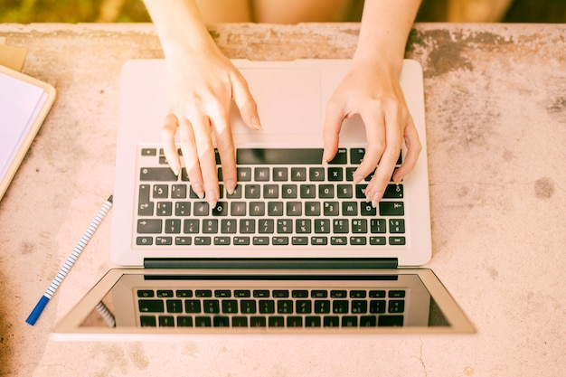 Anonymous woman sitting at desk and typing on laptop Free Photo