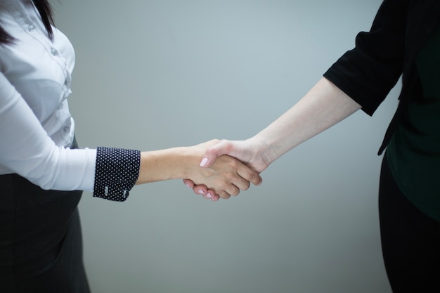 Anonymous women shaking hands on gray Free Photo