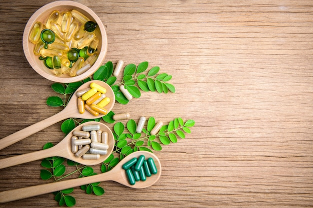Antioxidants vitamin capsule in wooden spoon, organic herbal medicine and supplemental on wooden background Premium Photo
