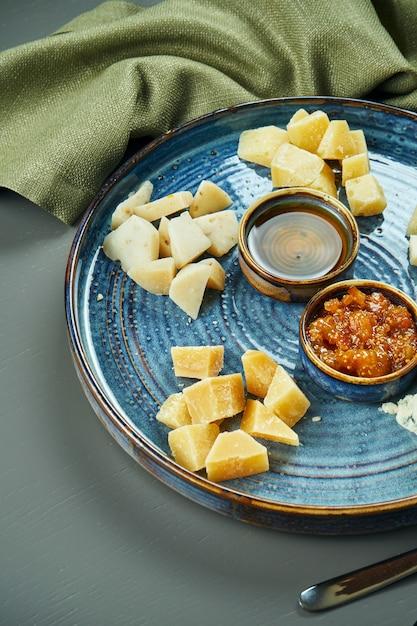 Антипасто - сырная тарелка. разные, домашние сыры на керамической тарелке - бри, камамбер, голландский с медом и орехами. винная закуска. крупным планом, селективный фокус, вертикальный Premium Фотографии
