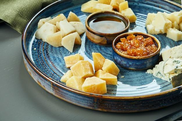 Антипасто - сырная тарелка. разные, домашние сыры на керамической тарелке - бри, камамбер, голландский с медом и орехами. винная закуска. крупным планом, селективный фокус Premium Фотографии