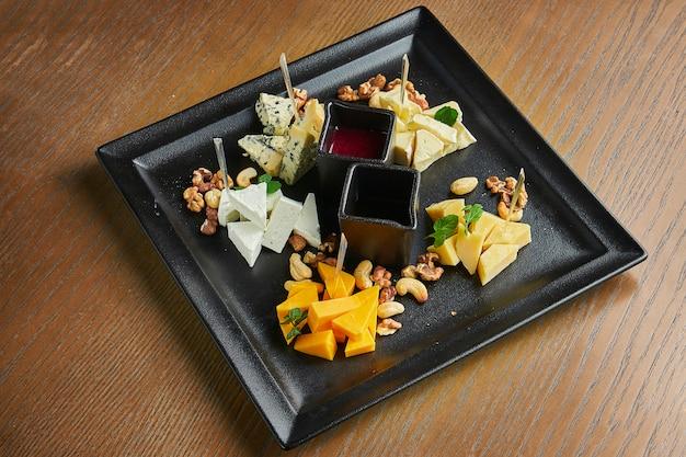 Антипасто - сырная тарелка. разные, домашние сыры на керамической тарелке - бри, камамбер, голландский с медом и орехами. винная закуска. вид сверху, плоская планировка, копия пространства. добавить шум на пост Premium Фотографии