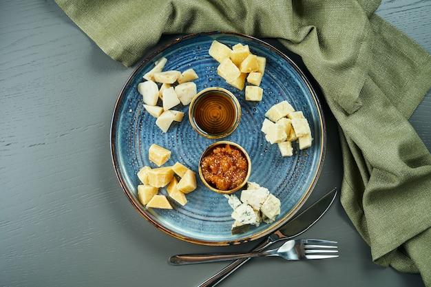 Антипасто - сырная тарелка. разные, домашние сыры на керамической тарелке - бри, камамбер, голландский с медом и орехами. винная закуска. вид сверху, плоская планировка, копирование пространства Premium Фотографии
