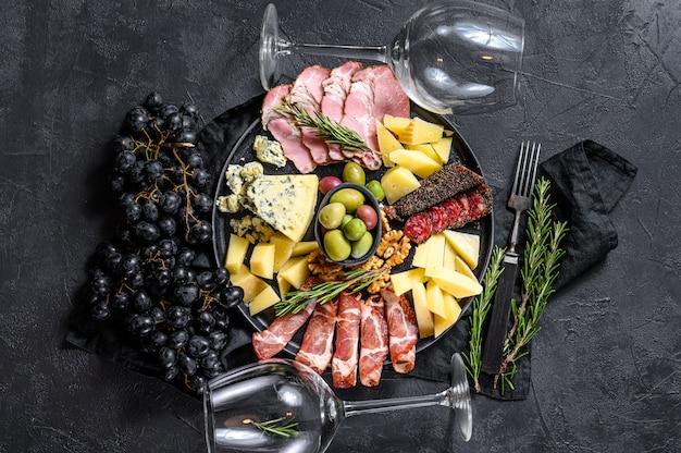 Антипасто доска с нарезанным мясом, ветчиной, салями, сыром, оливками. черная стена. вид сверху Premium Фотографии