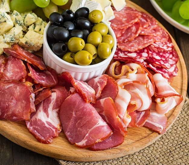Антипасто блюдо с беконом, вяленым мясом, салями, сыром и виноградом на деревянном столе Бесплатные Фотографии