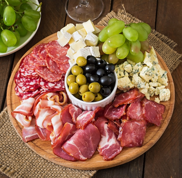 Antipasto catering platter with bacon, jerky, salami, cheese and grapes on a wooden table Free Photo