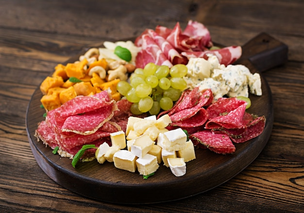 Antipasto catering platter with bacon, jerky, sausage, blue cheese and grapes Premium Photo
