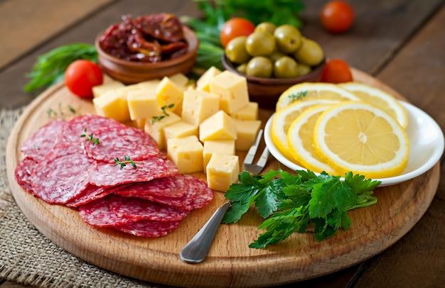 Антипасто блюдо с салями и сыром по дереву Premium Фотографии