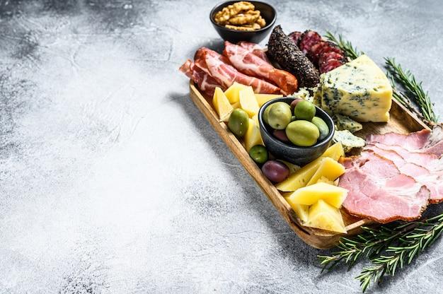 Антипасто с ветчиной, прошутто, салями, голубым сыром, моцареллой и оливками. серый фон вид сверху. пространство для текста Premium Фотографии