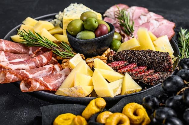 Antipasto platter with ham, prosciutto, salami, blue cheese, mozzarella and olives. top view Premium Photo