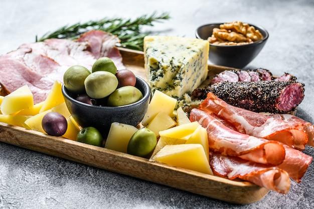 Антипасто различные закуски, разделочная доска с прошутто, салями, коппа, сыр и оливки. серая стена. вид сверху Premium Фотографии
