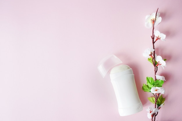 Antiperspirant or deodorant with white flowers on pink background. copy space Premium Photo
