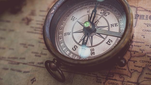 Antique bronze compass on old world map Premium Photo