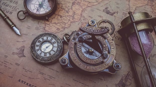 Antique bronze compass with pirate collection on old world map Premium Photo