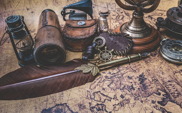 Antique bronze quill pen and old collection on old world map Premium Photo