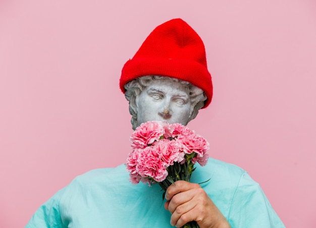 Antique bust of male in hat with carnations bouquet Premium Photo