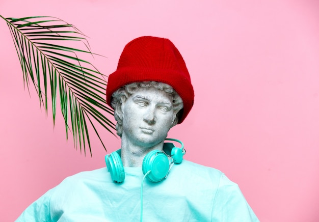 Antique bust of male in hat with headphones on pink background. Premium Photo