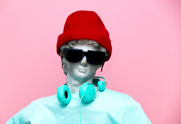 Antique bust of male in hat with headphones and sunglasses Premium Photo