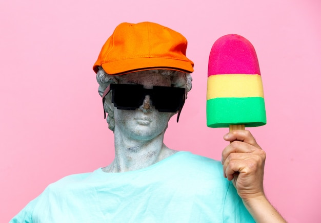 Antique bust of male in hat with sunglasses and toy ice-cream Premium Photo
