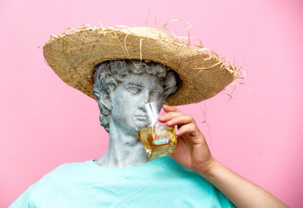 Antique bust of male in hat with whiskey glass Premium Photo