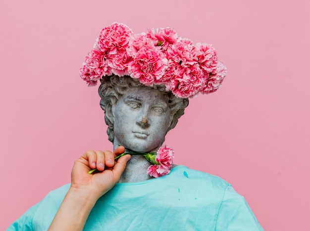 Antique bust of male with carnations bouquet in a hat Premium Photo