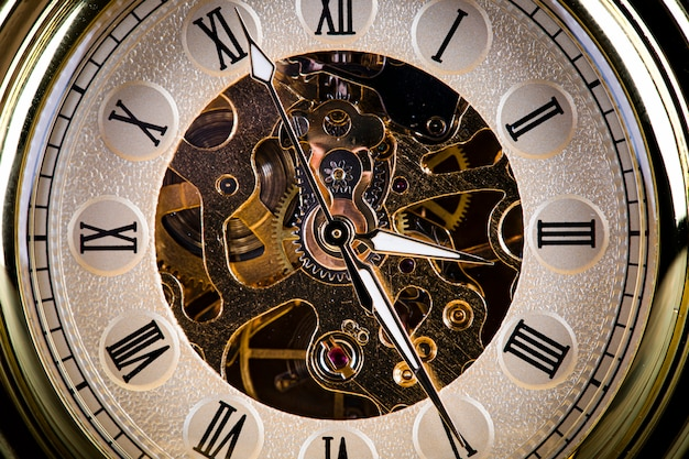 Antique clock on the background of vintage books. mechanical clockwork on a chain. Premium Photo