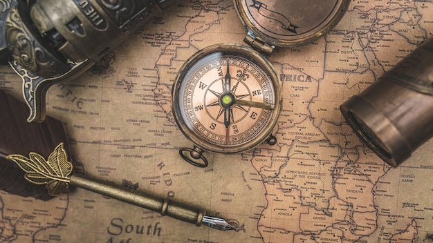 Antique compass and quill pen on old world map Premium Photo