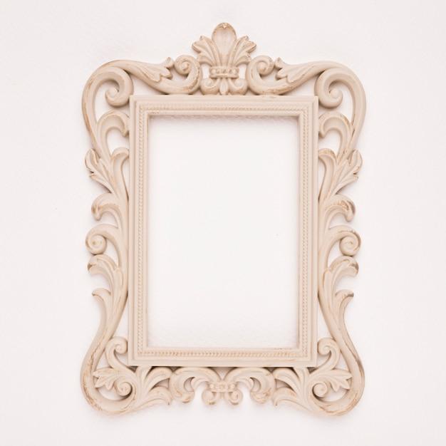 Antique gilded wooden frame on beige backdrop Free Photo