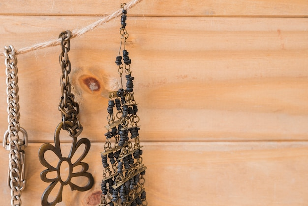 Antique metallic and beads bracelet hanging on jute string against wooden wall Free Photo