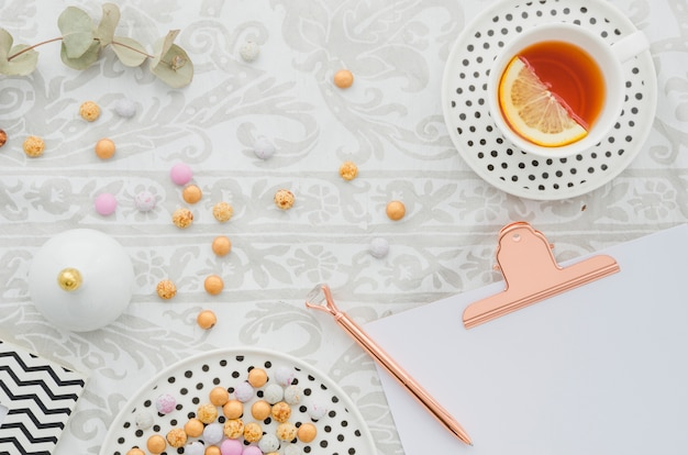 Antique pen on clipboard with candies and ginger lemon tea cup on tablecloth Free Photo