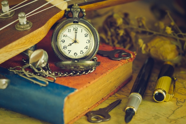 An antique pocket watch leaned against a ukulele and old book with vintage map Premium Photo