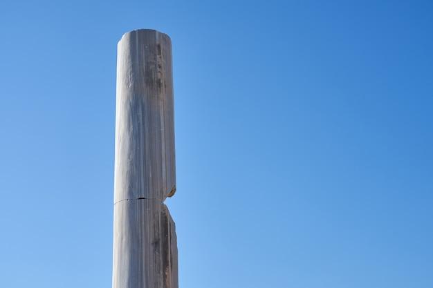 澄んだ青い空を背景のアンティークの石の列。 Premium写真